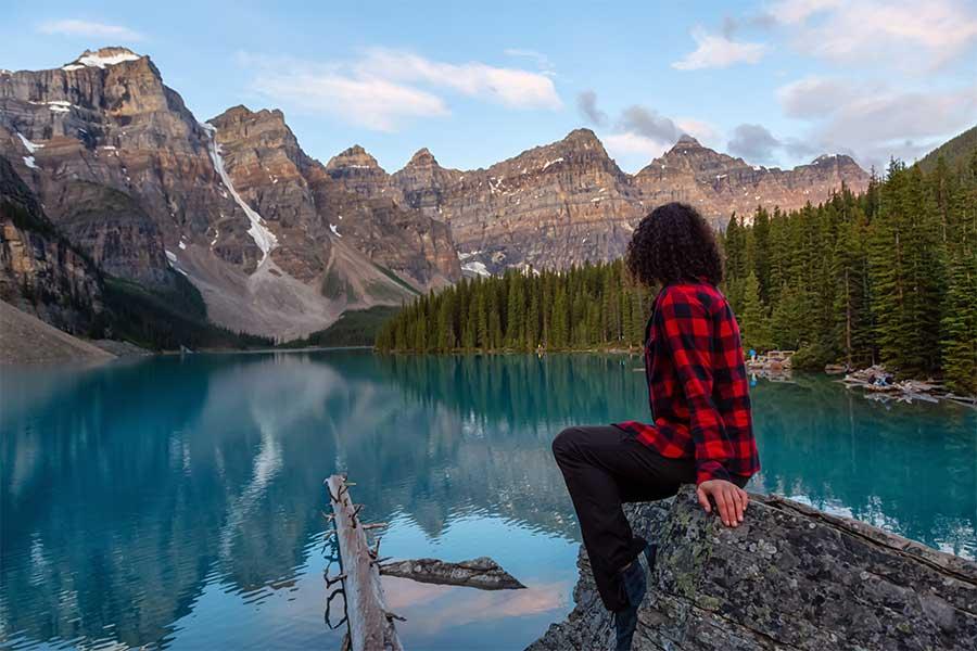 woman looking at mountain lake